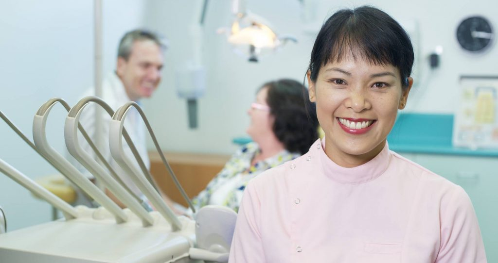 Dr Lo-An Vu with Dr Alan Fitzpatrick and the patient in the background | Dentist Arana Hills